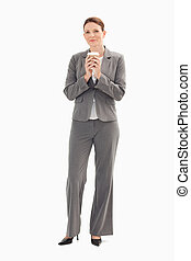 Businesswoman holding cup of coffee with both hands - A...