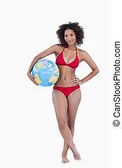Attractive brunette woman holding a beach ball