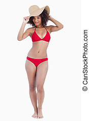 Young brunette woman standing upright in swimsuit