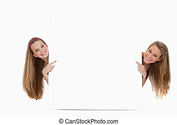 Portrait of wo long hair women back of a blank sign -...