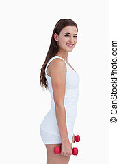 Side view of a smiling woman holding dumbbells