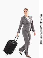 Smiling businesswoman walking with a suitcase - A...