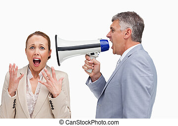 Businessman screaming after his colleague with a megaphone...