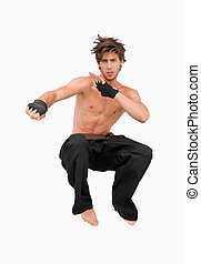 Jumping martial arts fighter against a white background