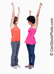 Two dynamic teenagers raising their arms in satisfaction