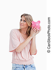 Woman holding a piggy bank up to her head