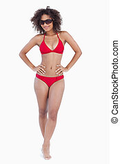 Attractive brunette standing upright in swimsuit