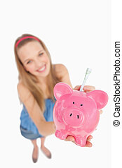 Fisheye view of a young woman putting money in a piggy-bank...