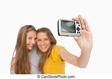 Two students taking a picture of themselves with a digital camera against white background