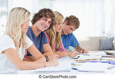 A group of students sitting together as they study hard with one man looking at the camera and smiling