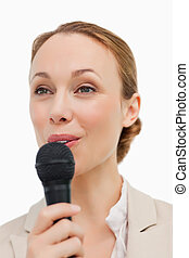 Woman in a suit speaking with a microphone