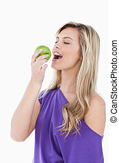 Blonde woman eating a green apple