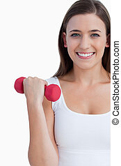 Smiling woman looking at the camera while holding a weight