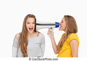 Blonde student using a loudspeaker on her friend against...