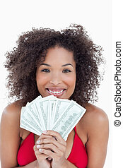 Smiling brunette holding a fan of bank notes against a white...