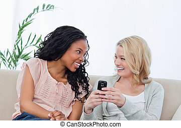 A woman holding a mobile phone is smiling at her friend