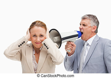 Businessman yelling with a megaphone after his colleague...