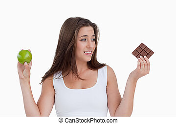 Young brunette woman holding a piece of chocolate and an apple