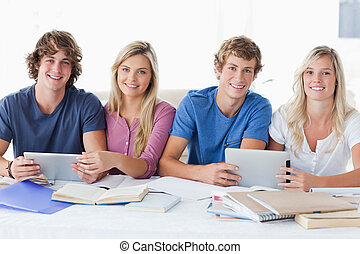 A smiling group of students looking at the camera - A...