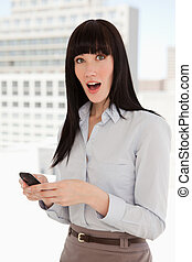 A woman at work with her mobile in hand looking up and shocked after reading her text message