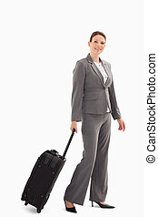 Businesswoman with suitcase walking - A businesswoman is...
