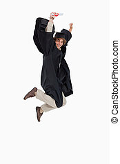 Happy male student in graduate robe jumping against white...