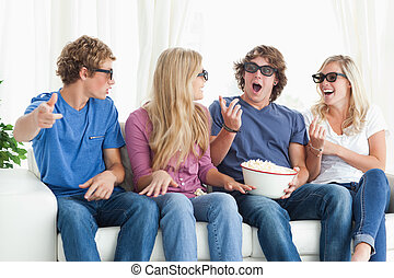 Friends laugh and joke around while watching a movie - A...