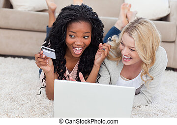 Two women are laughing and lying on the floor with a laptop...
