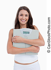Smiling woman holding weighing scales against a while...