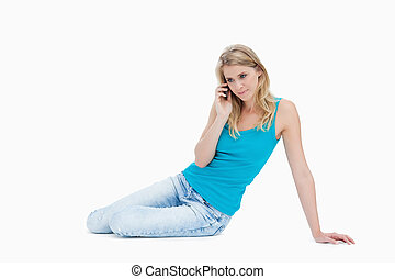 A woman sitting on the floor is talking on her mobile phone