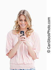 A smiling woman looking at her mobile phone - A smiling...