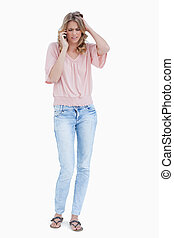 A full length shot of a frustrated woman talking on her mobile phone against a white background