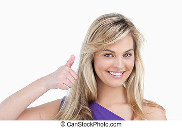 Smiling blonde woman placing her thumbs up against a white...