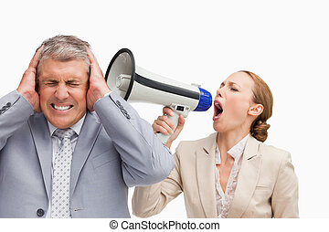 Businesswoman screaming with a megaphone after her colleague...