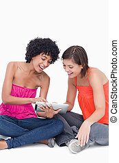 Laughing teenager showing a funny application on her tablet computer to a friend