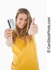 Portrait of a blonde student tending a credit card with the thumb