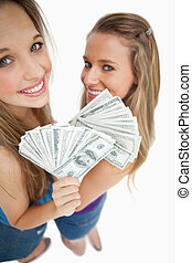 High-angle view of two young woman holding dollars against...