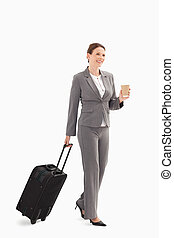 Businesswoman with coffee and suitcase - A businesswoman...