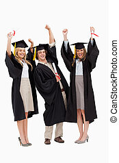 Three students in graduate robe raising their arms against...