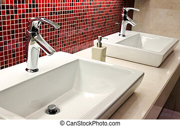 sinks and taps in a public toilet - sinks and taps in a...