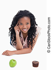 A woman woman is smiling at the camera with an apple  and bun in front of her against a white background