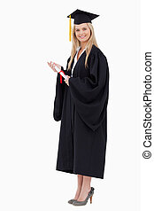 Blonde student in graduate robe holding a diploma