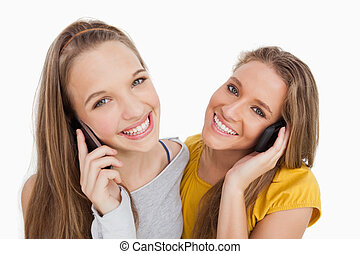 Close-up of two young women smiling on the phone against...