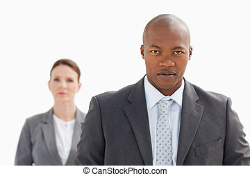 Businessman staring at camera with businesswoman behind him
