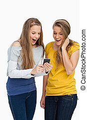 Two surprised students looking a cellphone screen against...