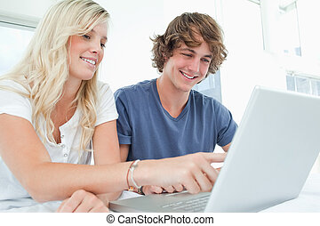 A smiling couple using a laptop while pointing at the screen...