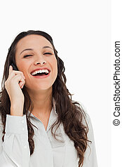 Portrait of a pretty brunette laughing while phoning