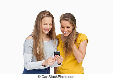 Two smiling students looking a cellphone screen