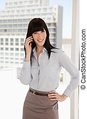 A smiling business woman taking a call - A business woman at...