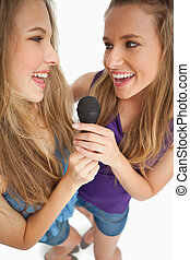 High-angle shot of two happy young beauty singing together...